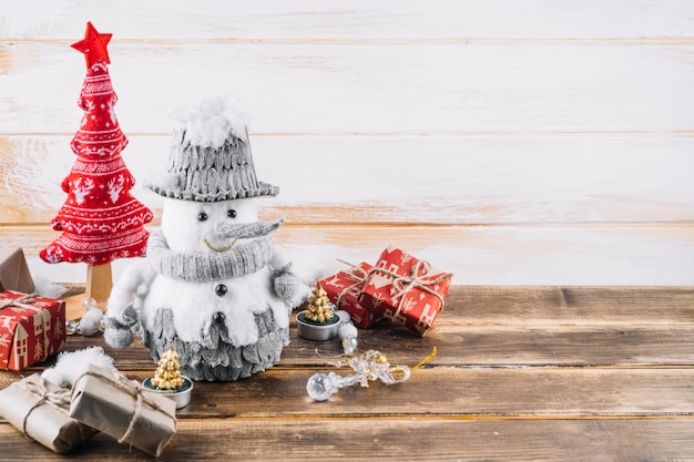 Kleine sneeuwpop met geschenkdozen op tafel