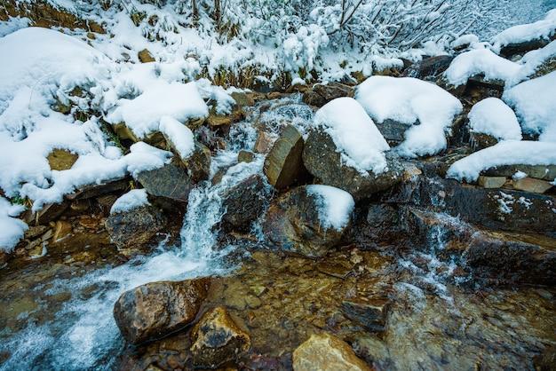 Kleine snelle stroom tussen kleine natte stenen en koude witte sneeuw in de pittoreske karpaten in het prachtige oekraïne en zijn fantastische natuur