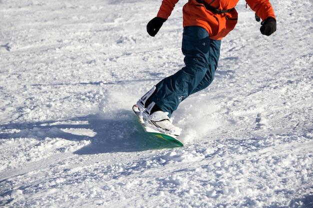 Kleine snowboarder op blauwe hemelachtergrond.