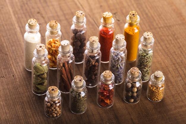 Kleine souvenirflessen met kruiden over houten tafel