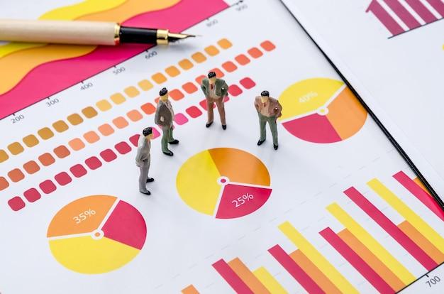 Kleine speelgoedmensen: zakenmanstandaard met analyse van financiële grafieken.