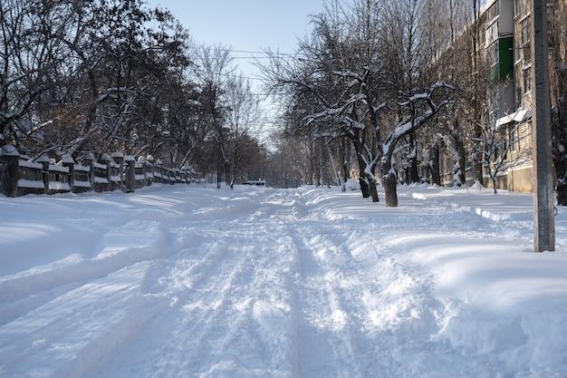 Kleine stad bedekt met sneeuw. kleine gebouwen en huizen in de winter met veel sneeuw in een straat.