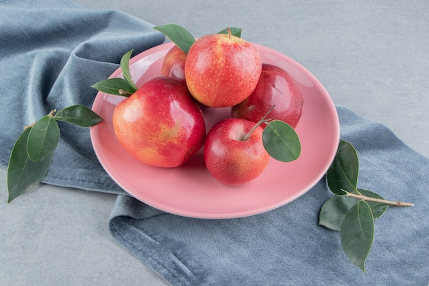 Kleine stapel appels op een schaal op een stuk stof op marmer.