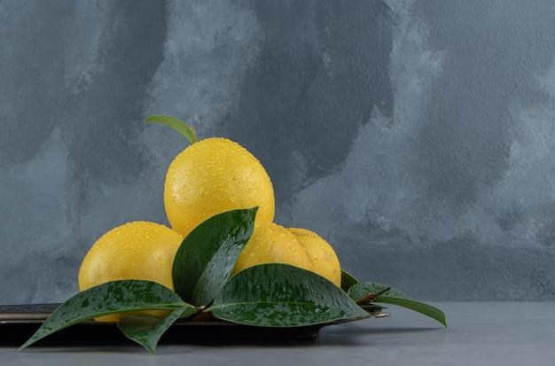 Kleine stapel citroenen en bladeren op een sierlijk dienblad op marmer