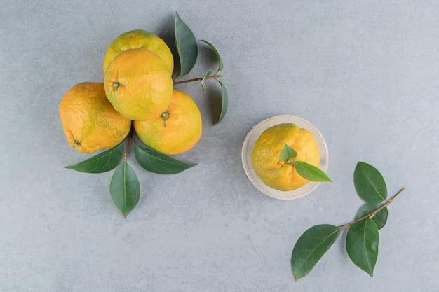 Kleine stapel mandarijnen en bladeren op marmer.