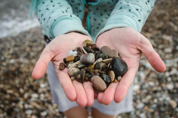 Kleine steentjes van verschillende kleuren vasthouden op het strand