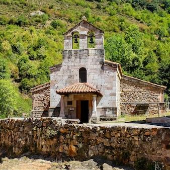 Kleine stenen kapel naast oude stenen muur in het groene veld. asturië spanje.