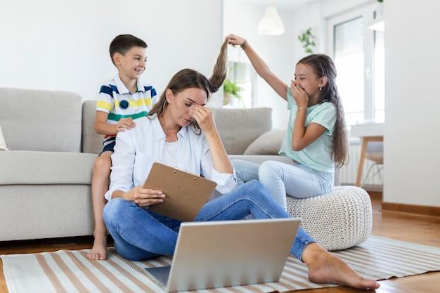 Kleine stoute kinderen die de drukke jonge vrouw afleiden van het werk op de laptop thuis