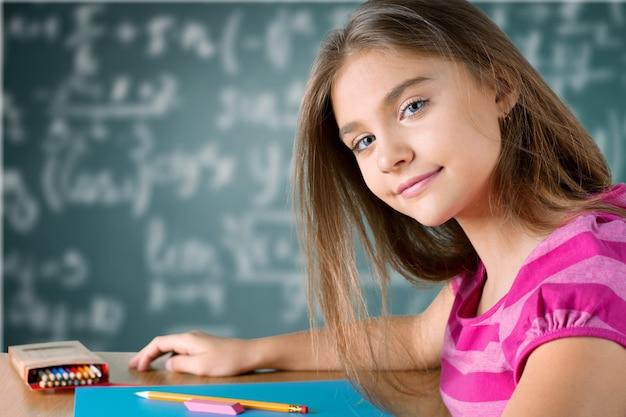 Kleine student meisje studeren op achtergrond