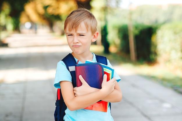 Kleine student met negatieve emoties gaat naar school. onderwijs, terug naar schoolconcept.