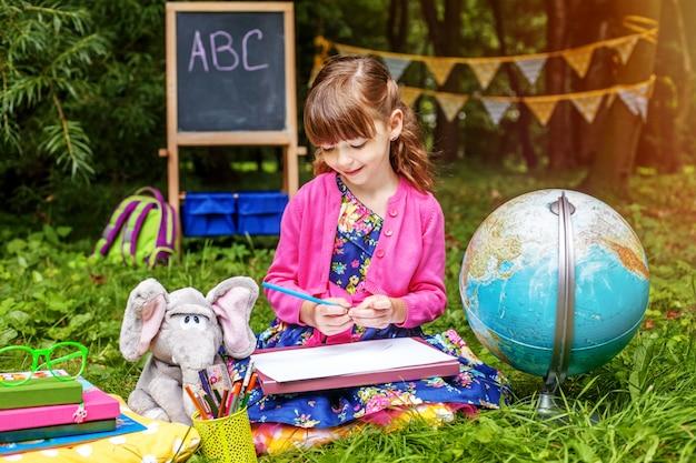 Kleine student schrijft in een notitieblok. wereldbol.
