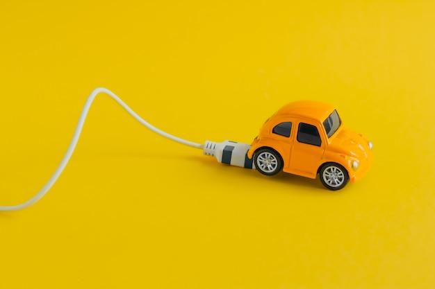 Kleine stuk speelgoed auto met het laden van kabel die op geel wordt geïsoleerd