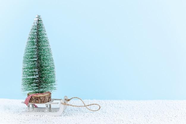 Kleine stuk speelgoed boom op een slee op een blauwe achtergrond. kerst concept.