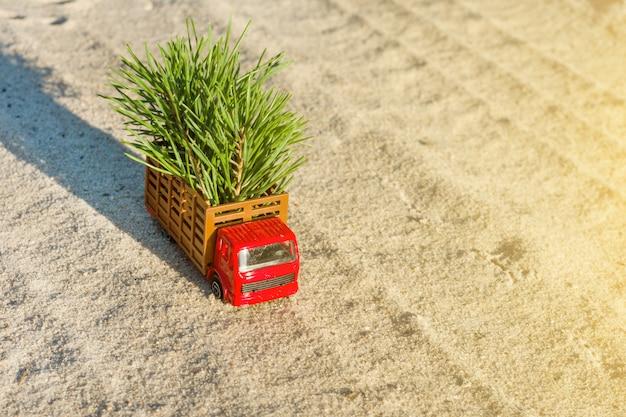 Kleine stuk speelgoed vrachtwagen met kerstboom op bosweg