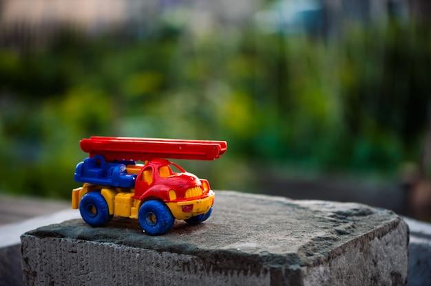 Kleine stuk speelgoed vrachtwagen met kraantribunes op schuimblok op groen gras.