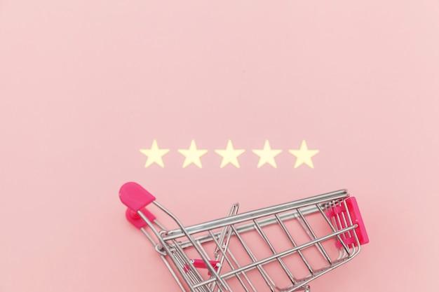 Kleine supermarkt duwen kar voor winkelen speelgoed met wielen en 5 sterren rating geïsoleerd op pastel roze achtergrond. kleinhandelsconsument die online evaluatie en herzien concept kopen.