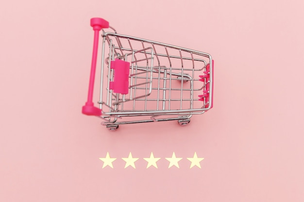Kleine supermarkt kruidenier duwkar om te winkelen speelgoed met wielen en 5 sterren waardering geïsoleerd op pastel roze achtergrond. detailhandelaar die online evaluatie- en beoordelingsconcept koopt.