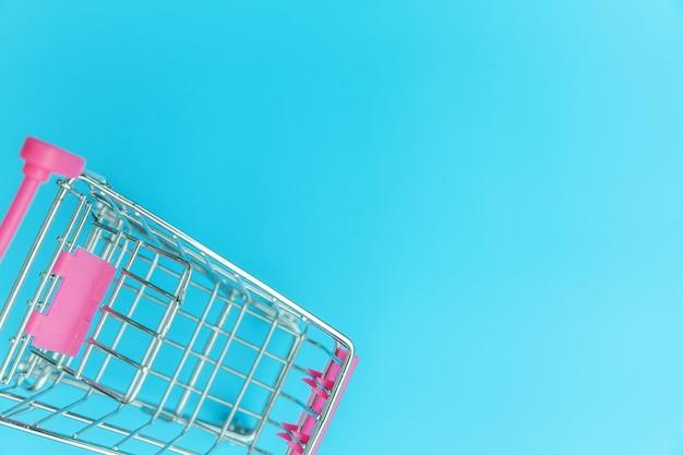 Kleine supermarkt kruidenier duwkar voor het winkelen speelgoed geïsoleerd op blauwe achtergrond