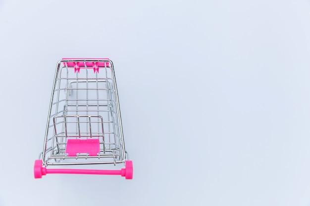 Kleine supermarkt kruidenier duwkar voor het winkelen speelgoed geïsoleerd op een witte achtergrond