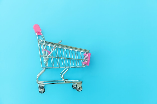 Kleine supermarkt kruidenier duwkar voor het winkelen speelgoed met wielen geïsoleerd op blauw pastel kleurrijk trendy