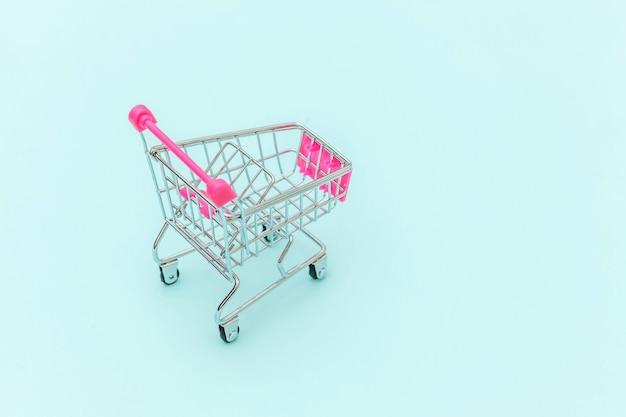 Kleine supermarkt kruidenier push kar voor winkelen speelgoed met wielen geïsoleerd op blauwe pastel kleurrijke trendy achtergrond kopie ruimte. verkoop koop winkelcentrum markt winkel consument concept.