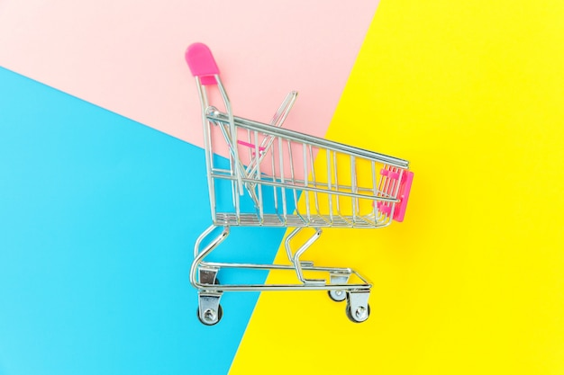 Kleine supermarkt push kar voor winkelen speelgoed geïsoleerd op blauw geel roze achtergrond