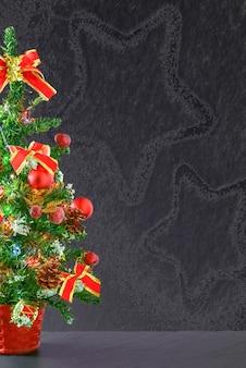 Kleine tafel kerstboom versierd met rode ornamenten en strikken op een grijze achtergrond