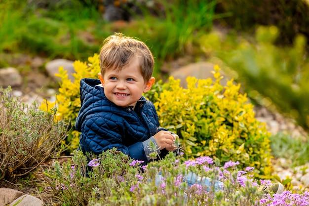 Kleine todler spelen met bloemen in de tuin