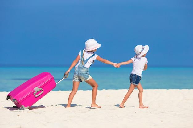 Kleine toeristenmeisjes met grote koffer op tropisch wit strand