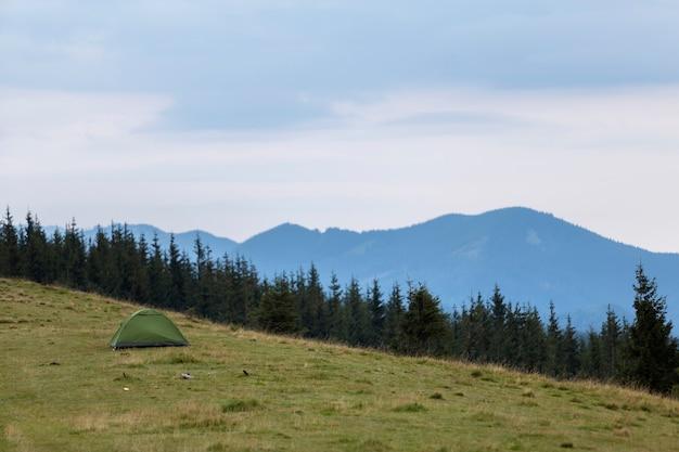 Kleine toeristentent op grasrijke bergheuvel. zomer kamperen in bergen bij dageraad. toerisme .