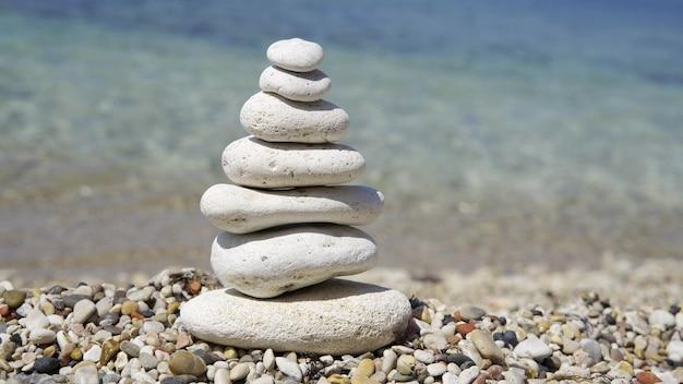 Kleine toren gemaakt van stenen. de kiezelstenen worden op elkaar gestapeld. stenen piramide op een achtergrond van water. close-up, 4k uhd.
