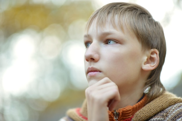 Kleine trieste jongen in een warme trui voor een wandeling in de herfst