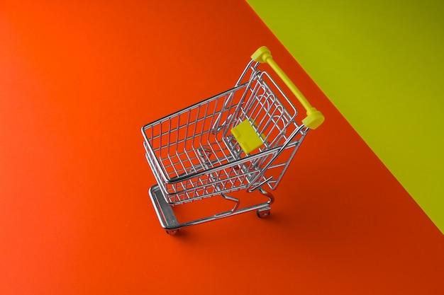 Kleine trolley op een oranje en gele voorgrondtafel. blackfriday en cybermonday concept