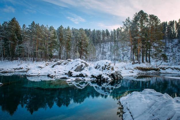 Kleine turquoise meer in de bergen tussen besneeuwde bossen.