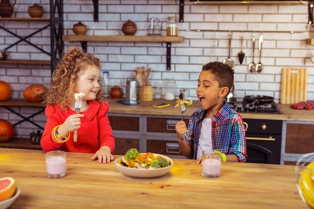 Kleine vegetariërs. vrolijk blond meisje dat vork met bloemkool houdt en naar haar vriend kijkt
