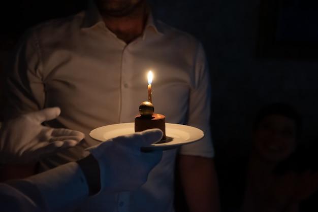 Kleine verjaardagstaart met een enkele kaars die wordt gepresenteerd door een ober of server