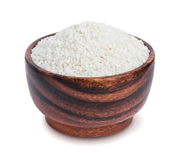 Kleine verpletterde rijst in houten die kom op witte achtergrond wordt geïsoleerd