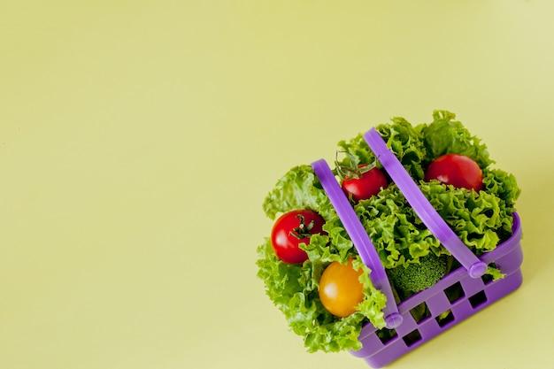 Kleine verse groenten in mand op geel. eten met copyspace