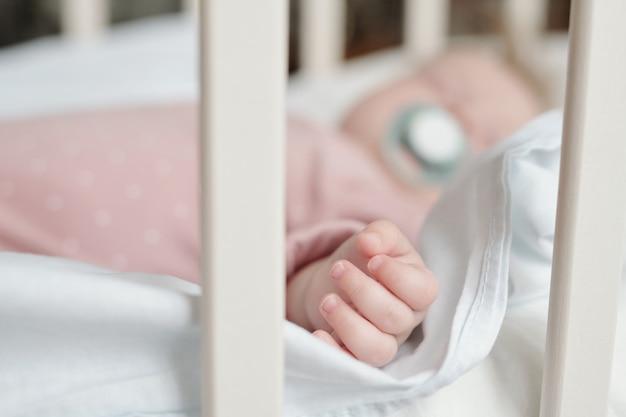 Kleine vingers en hand van babymeisje die in wieg slapen