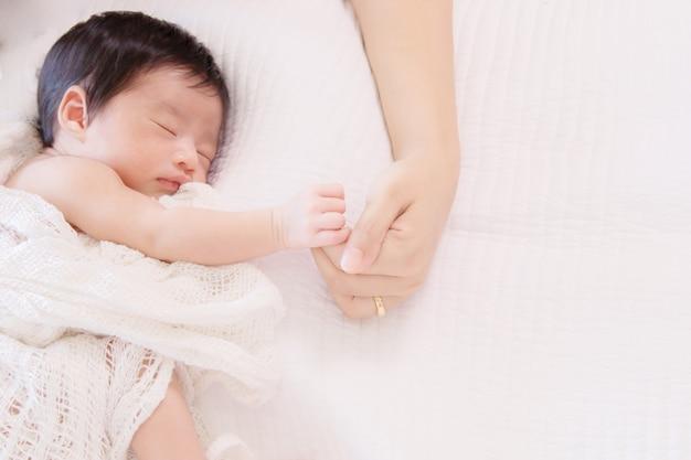 Kleine vingers van pasgeboren baby houden moeders handen vast