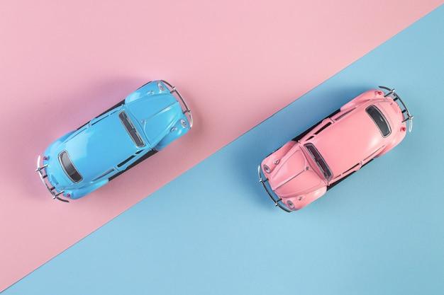Kleine vintage retro speelgoedauto's op een roze en blauwe achtergrond