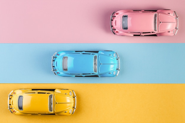 Kleine vintage retro speelgoedauto's op een roze, gele en blauwe achtergrond
