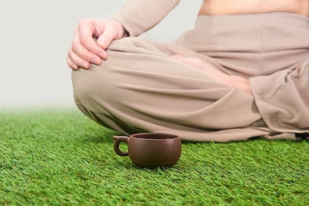 Kleine vintage theekop van klei op grastapijt naast vrouw die in lotushouding zit