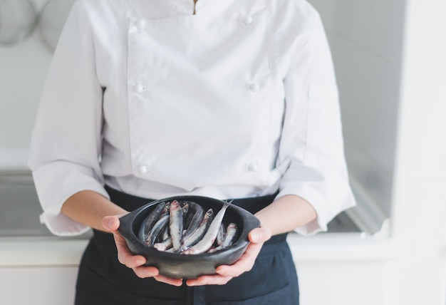 Kleine vissen in keramische kom over handen van de chef.