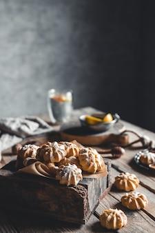 Kleine vla cakes in houten kist en kopje koffie op bruin houten tafel