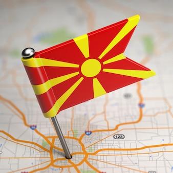 Kleine vlag republiek macedonië op de achtergrond van een kaart met selectieve aandacht.