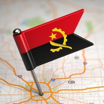 Kleine vlag van angola op de achtergrond van een kaart met selectieve aandacht.