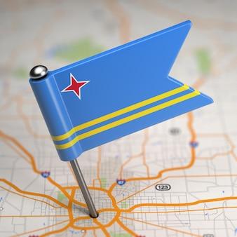 Kleine vlag van aruba op de achtergrond van een kaart met selectieve aandacht.