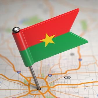 Kleine vlag van burkina faso op de achtergrond van een kaart met selectieve aandacht.