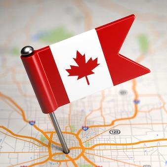Kleine vlag van canada op de achtergrond van een kaart met selectieve aandacht.